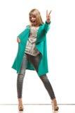 Пальто женщины зеленое показывая знак победы Стоковое фото RF
