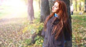 Пальто листьев осени девушки Стоковое фото RF