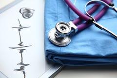 Пальто доктора с стетоскопом на столе Стоковые Фото