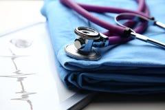 Пальто доктора с стетоскопом на столе Стоковое фото RF