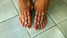 Пальцы ноги и пальцы с bi-цветом nailpolish на плиточном поле Стоковое Изображение RF