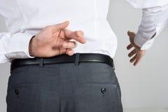Пальцы скрещивания бизнесмена пока предлагающ рукопожатие Стоковая Фотография RF