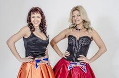 Певица актрисы 2 девушек в платьях коктеиля белокурых и коричневых волосах Стоковые Фото