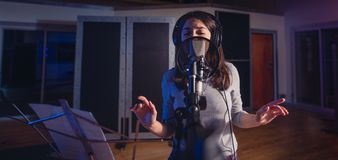Певица поя песню в студии звукозаписи стоковое изображение rf