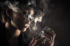 Певица с ретро дымом микрофона и сигареты Стоковые Изображения RF