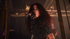 Певица эмоционально кричит в микрофоне на представлении рок-группы видеоматериал
