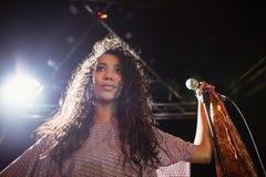 Певица Thougthful молодая держа mic на ночном клубе стоковые фотографии rf