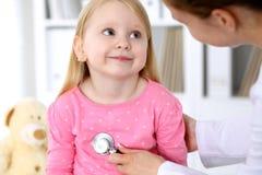 Педиатр позаботится о младенец в больнице Маленькая девочка рассматривает доктором стетоскопом здоровье внимательности рукояток и Стоковые Фотографии RF