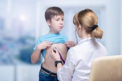 Педиатр рассматривает подросткового ребенка на встрече стоковые фото
