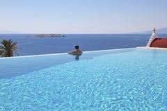 Пейзажный бассейн и человек Mykonos Стоковые Изображения