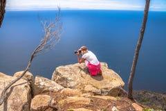 Пейзаж женщины фотографируя на скале в Тасмании Стоковые Изображения RF