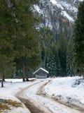Пейзаж зимы, снежная дорога и небольшой дом Стоковое фото RF