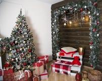 Пейзаж Нового Года внутри помещения Украшенная зеленая рождественская елка серия подарков Зона с подушкой и красным медведем стоковые фото