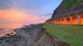 Пейзаж прибрежного шоссе скалистым пляжем перед восходом солнца со светами от тоннеля сарая утеса стоковая фотография rf