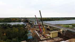 Пейзаж района строительства моста с проезжей частью и рекой 2 кранов близрасположенной акции видеоматериалы