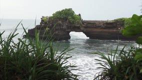 Пейзаж сини развевает приходить через отверстие в утесе на море, и падать на берега акции видеоматериалы