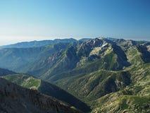 Пейзаж скалистой горы с лугом и голубым небом и облаками стоковое изображение