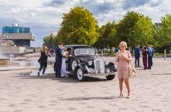 Пейзаж с женихом, невестой, винтажным автомобилем, фотографом и обычные люди на embankmen реки Днепр стоковое фото rf