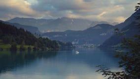 Пейзаж Швейцарии, высокие горы, зеленый лес, маленький город под высокими пиками, глубокое озеро с белым плаванием шлюпки видеоматериал