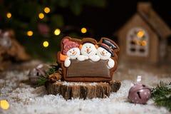 Пекарня еды праздника традиционная Snowmans потехи пряника 3 в уютном теплом украшении со светами гирлянды стоковое фото