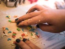 Пекарня рождества: Маленькая девочка собирая съестные письма для печений стоковые изображения