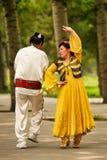 Пекин, Китай 07 06 Женщина 2018 в желтом танце человека платья и усика в парке стоковое изображение