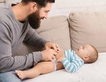Пеленка отца изменяя к его плача сыну младенца стоковые фото