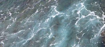 Пена и волны зеленоватой голубой воды океана - абстрактные естественные предпосылка и текстура Aqua стоковое фото rf
