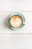 Пена капучино, взгляд сверху кофейной чашки на белой деревянной предпосылке Стоковые Фото