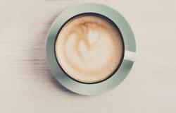 Пена капучино, взгляд сверху кофейной чашки на белой деревянной предпосылке Стоковые Изображения