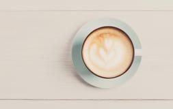 Пена капучино, взгляд сверху кофейной чашки на белой деревянной предпосылке Стоковая Фотография