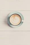 Пена капучино, взгляд сверху кофейной чашки на белой деревянной предпосылке Стоковая Фотография RF