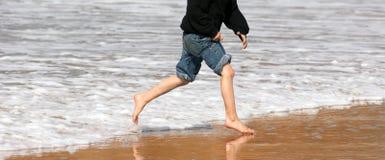 Пена моря молодого прибоя пляжа океана идущих ног мальчика разбивая Стоковое Изображение