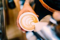 Пена latte профессионального barista лить над кофе, эспрессо и создавать совершенное капучино стоковое фото rf