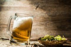 Пенистое пиво полило от чашки стоя на linen ткани Стоковое Фото