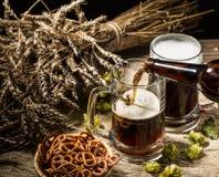 Пенообразное пиво от бутылки полило в кружку стоя с полным пивом кружки с пшеницей и хмелями, корзиной кренделей Стоковое Фото