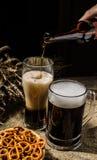 Пенообразное пиво от бутылки полило в glasse стоя с пивом кружки с пшеницей и корзиной кренделей Стоковое Изображение