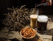 Пенообразное пиво от бутылки полило в glasse стоя с пивом кружки с пшеницей и корзиной кренделей Стоковая Фотография RF