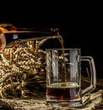 Пенообразное пиво полило в кружку стоя на пустой деревянной предпосылке Стоковые Изображения