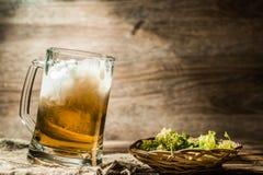 Пенообразное пиво полило от чашки стоя на linen ткани Стоковая Фотография RF