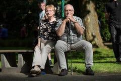 2 пенсионера на суде minigolf ждут на скамейке в парке a Стоковая Фотография
