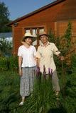 2 пенсионера против деревянного дома Стоковая Фотография