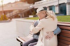 2 пенсионера сидят на стенде в квадрате Они нежно обнимают сидеть на стенде Стоковые Изображения RF