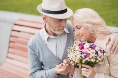 2 пенсионера сидят на стенде в переулке Пожилой человек нежно держит ее руку Стоковая Фотография RF