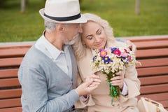 2 пенсионера сидят на стенде в переулке Пожилой человек нежно держит ее руку Стоковое Изображение