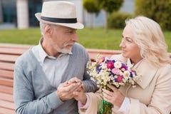 2 пенсионера сидят на стенде в переулке Постаретый человек дал женщине цветки Он держит ее руку Стоковые Фото
