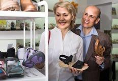 2 пенсионера совместно выбирая пары ботинок в магазине моды Стоковые Фотографии RF