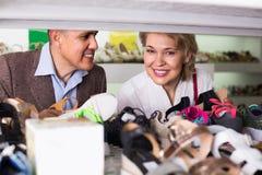 2 пенсионера совместно выбирая пары ботинок в магазине моды Стоковое фото RF