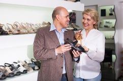 2 пенсионера совместно выбирая пары ботинок в магазине моды Стоковая Фотография
