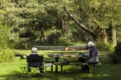 2 пенсионера с серым вьющиеся волосы сидя в тени стоковая фотография